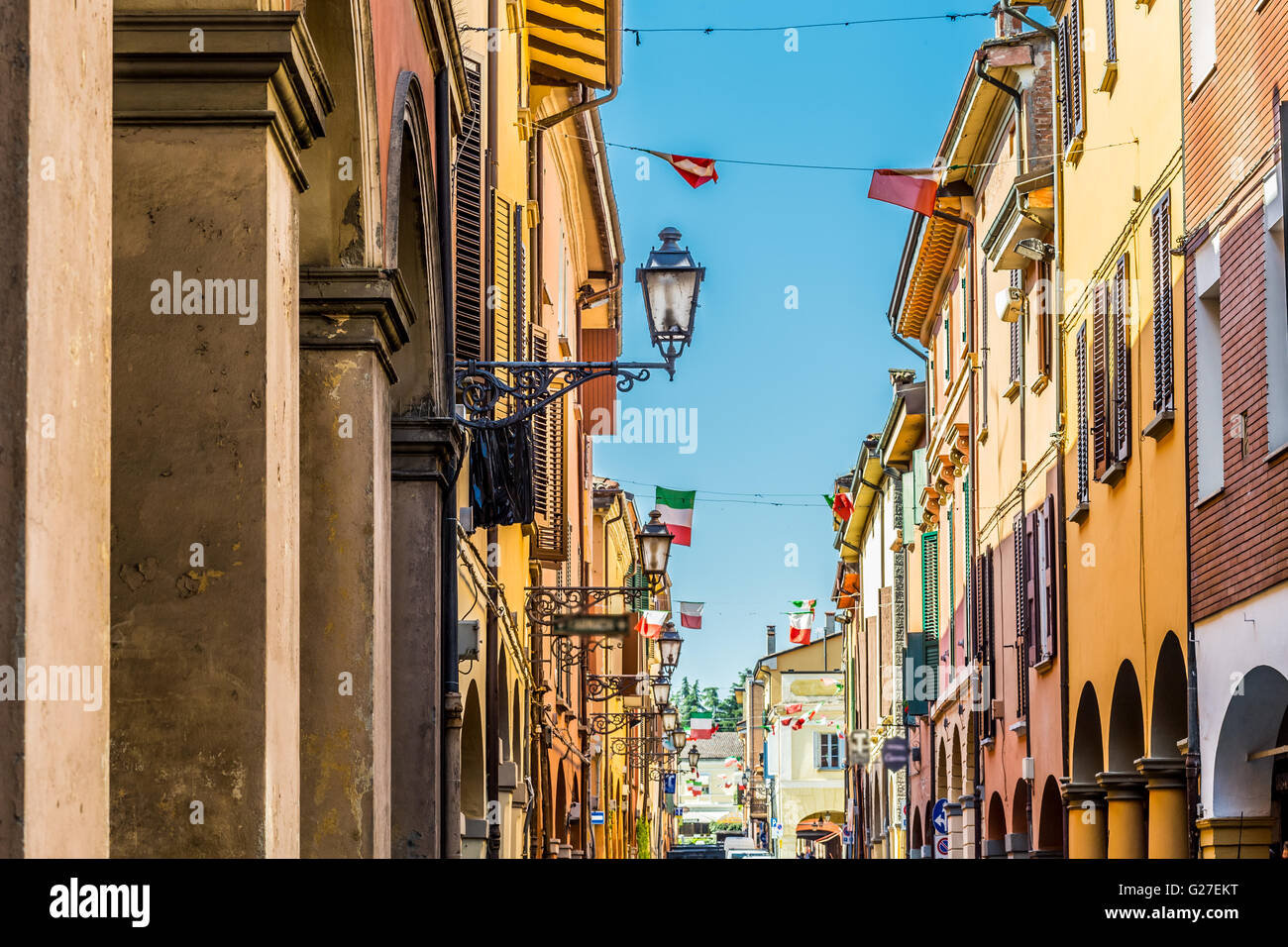 old city street with colorful houses and waving Italian flags - Stock Image