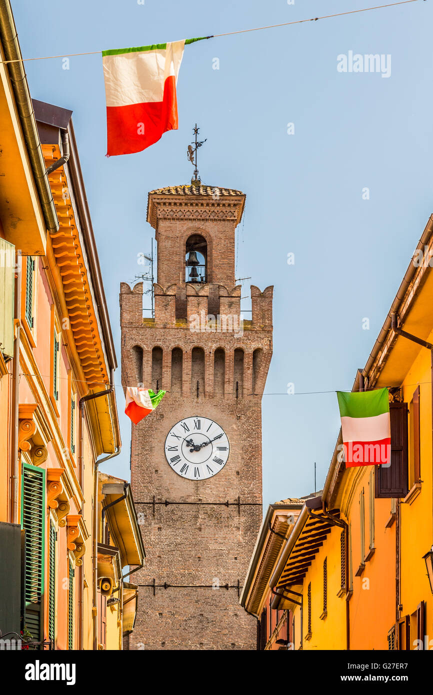 old city street with colorful houses, clock tower and waving Italian flags - Stock Image