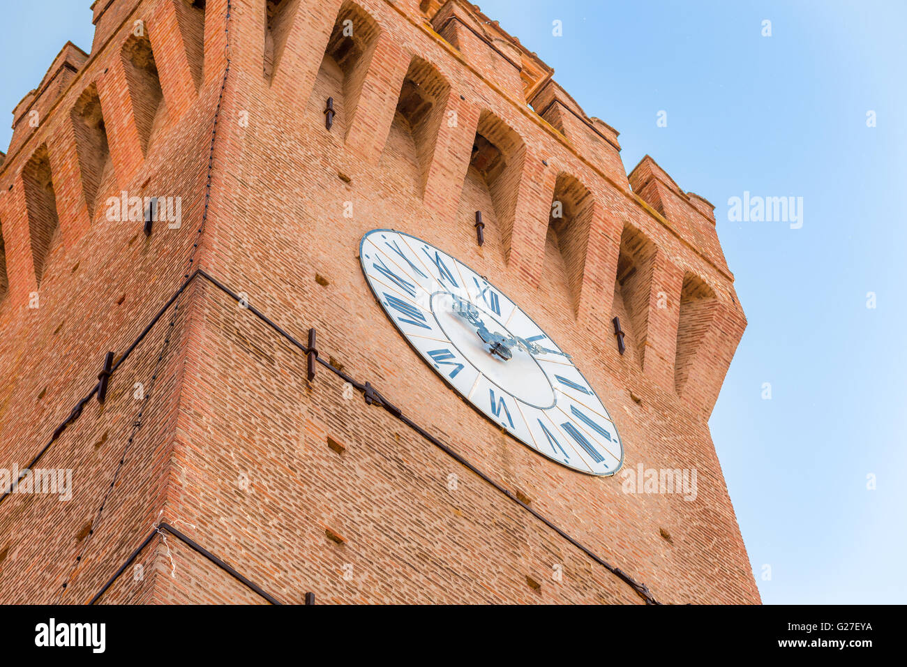 clock tower with Ghibelline battlements and buttresses - Stock Image