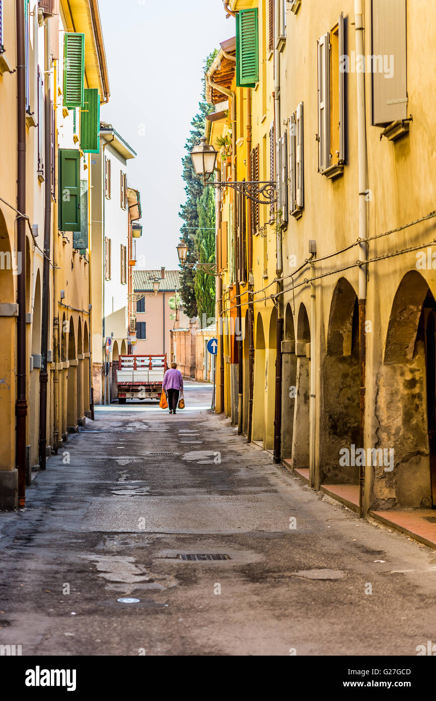 old woman with two large shopping bags walking in an old city street with colorful houses - Stock Image