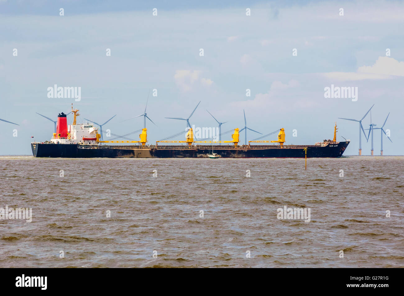 Bulk carrier Yick Luk passing in front of offshore windfarm seen from Crosby Merseyside - Stock Image