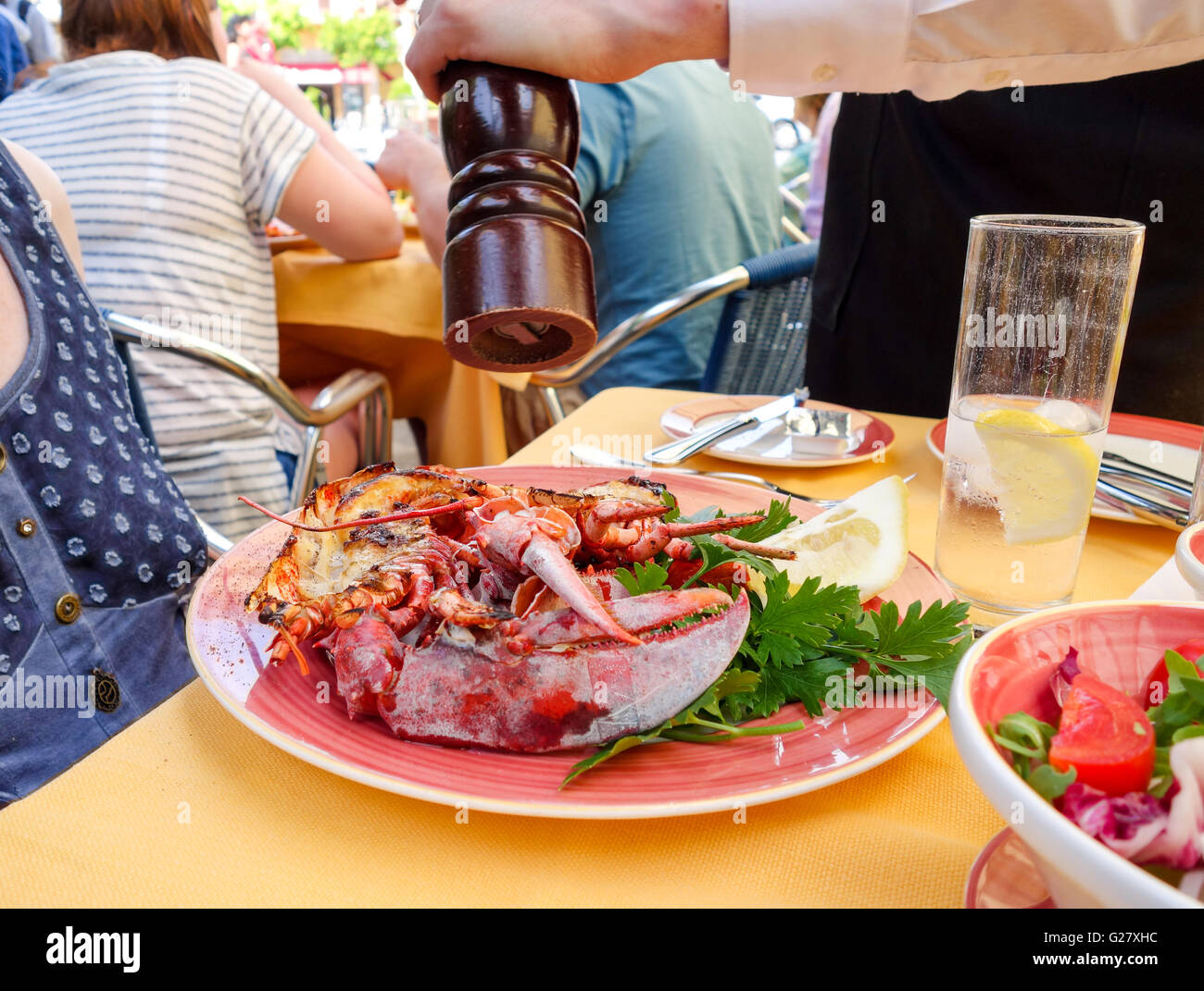 A Lobster dinner being sprinkled with black pepper from a pepper mill served outside at an outdoor cafe restaurant - Stock Image