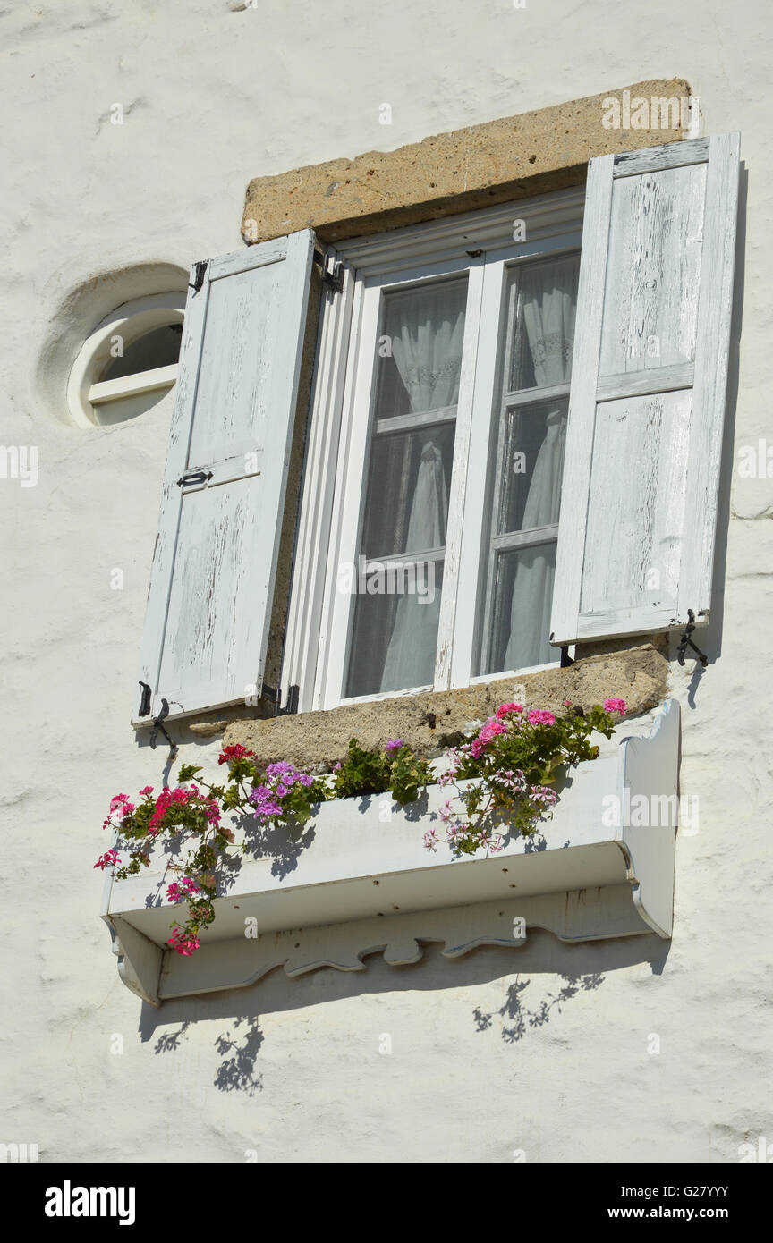 White open shutters on a white wood timber glazed window in a white washed wall with a window box of colourful flowers, - Stock Image