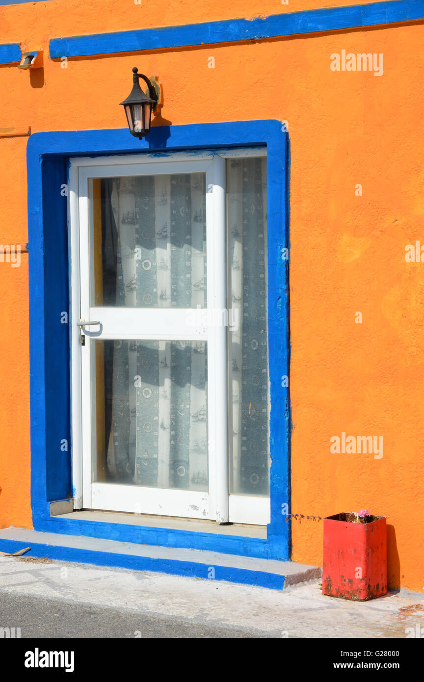 a white glazed wood timber door in a white frame with blue outline frame, in an orange paint render plaster wall, Stock Photo