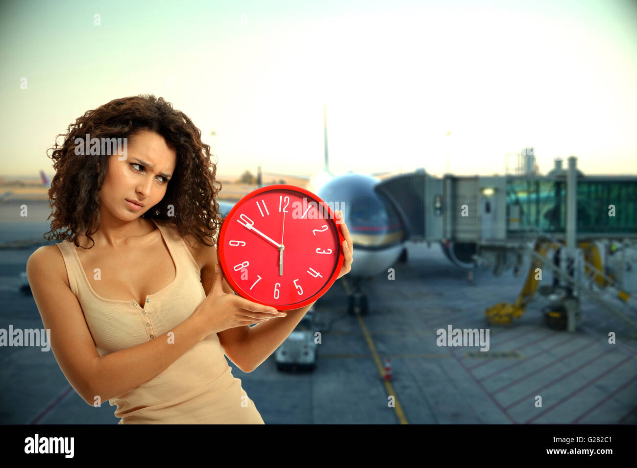 A lady looking upset to the clock at the airport for flight delay - Stock Image