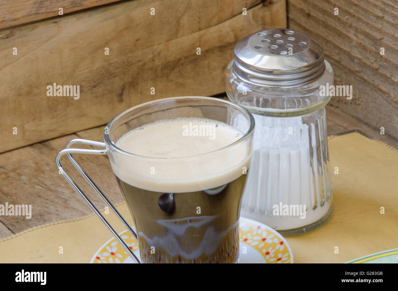 Cup of creamy black coffee with pallet wood background - Stock Image