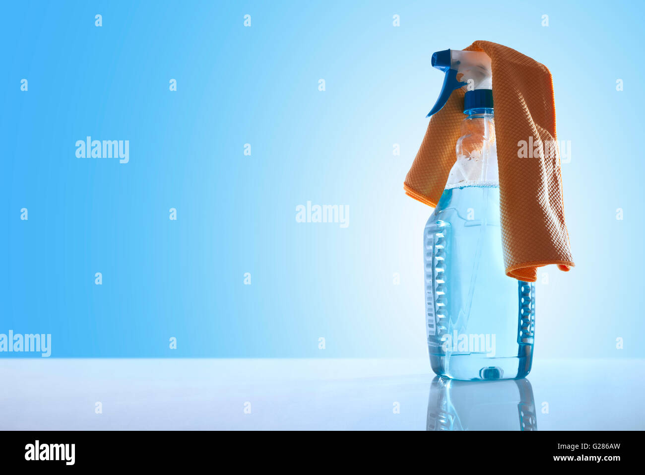 Bottle with glass cleaner and a yellow rag on a white table glass with blue background overview. Front view. Horizontal - Stock Image