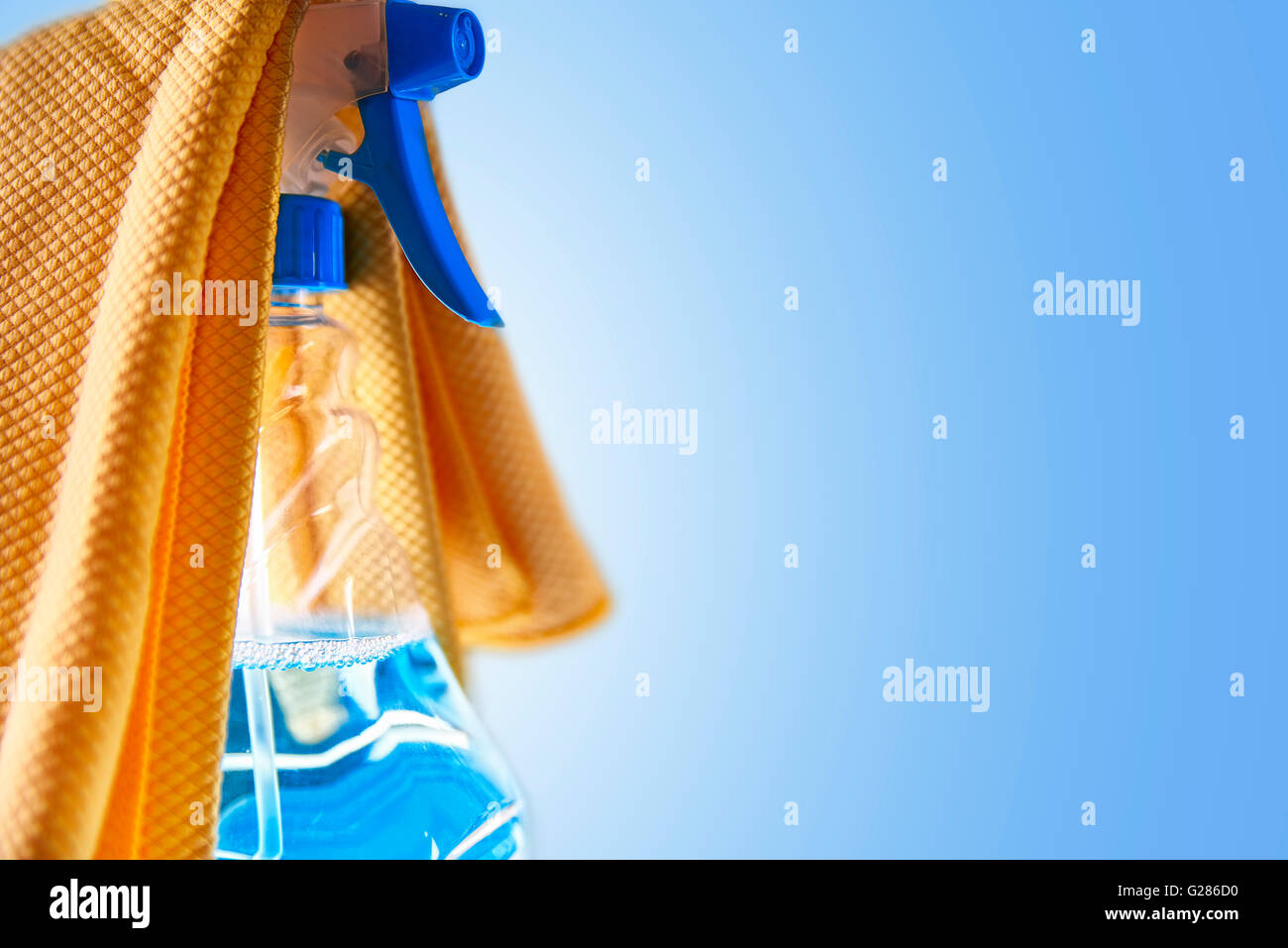 Glass cleaner spray bottle and yellow cloth with blue background. Cleaning concept.Horizontal composition. - Stock Image