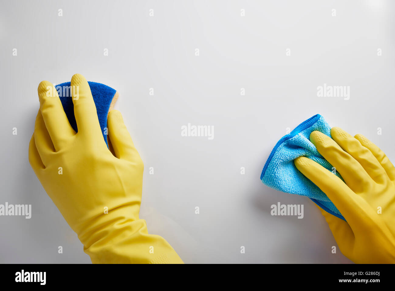 Hands of cleaning staff with rag and scourer working on white table. Top view. Horizontal composition. - Stock Image