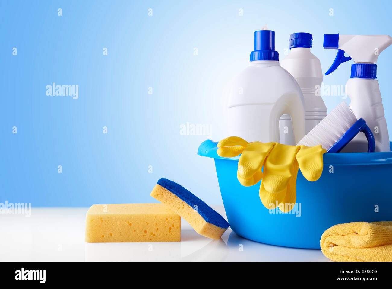 Professional cleaning equipment on white table and blue background overview. Cleaning tools company concept. Front - Stock Image