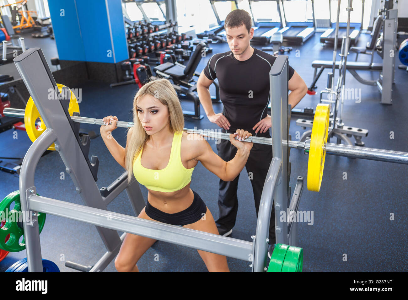 fitness woman and personal trainer in gym - Stock Image