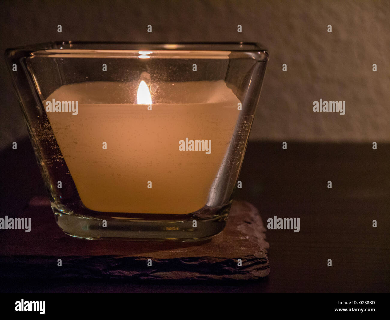 Single candle in glass holder, neutral background - Stock Image
