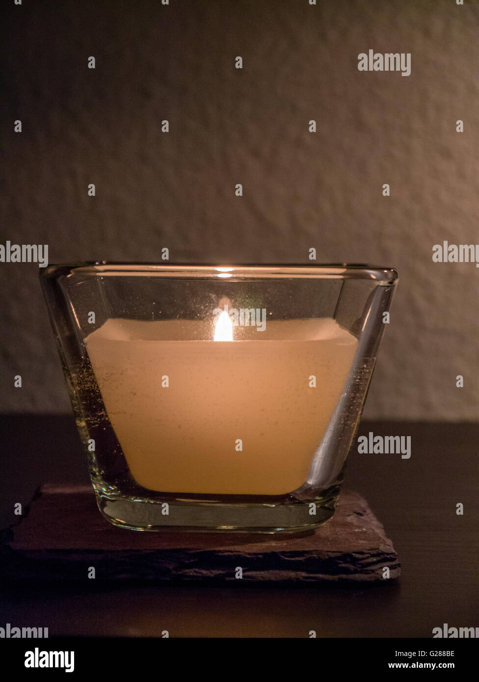 Close-up of lit candle, neutral background - Stock Image