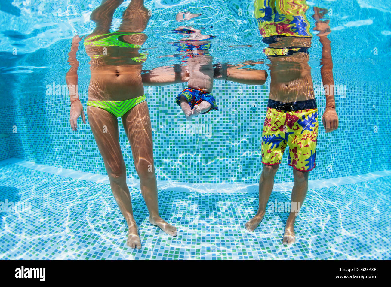 Happy swimming family - father and mother with baby swim and dive underwater with fun in pool. Healthy lifestyle, - Stock Image