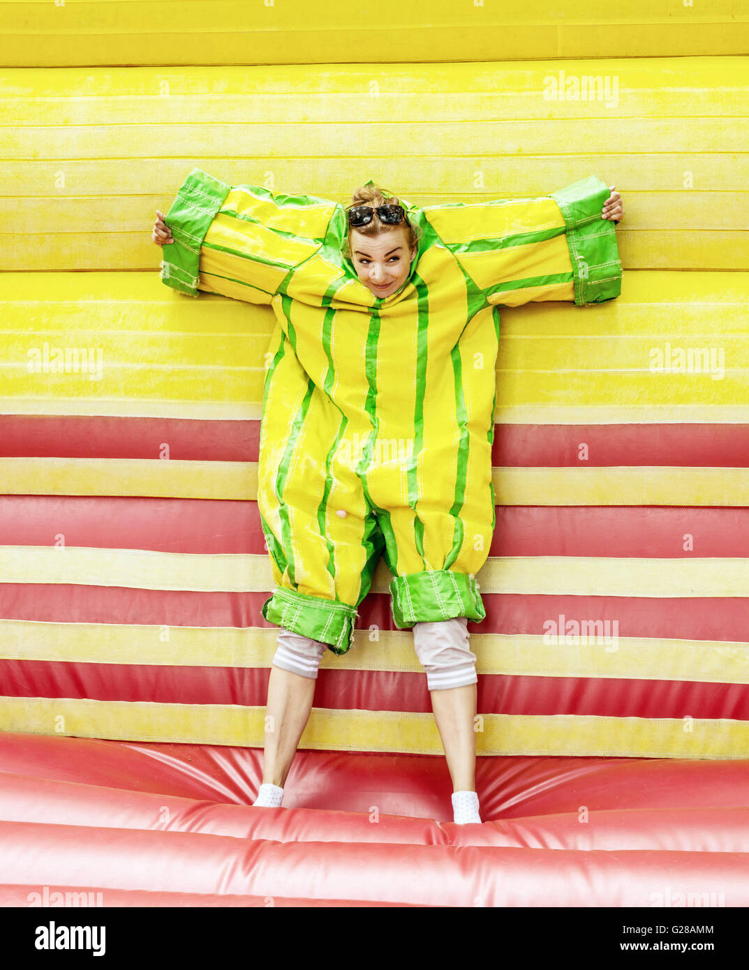 Joyful young caucasian woman in plastic dress in a bouncy castle imitates a fly on velcro wall. Inflatable attraction. - Stock Image