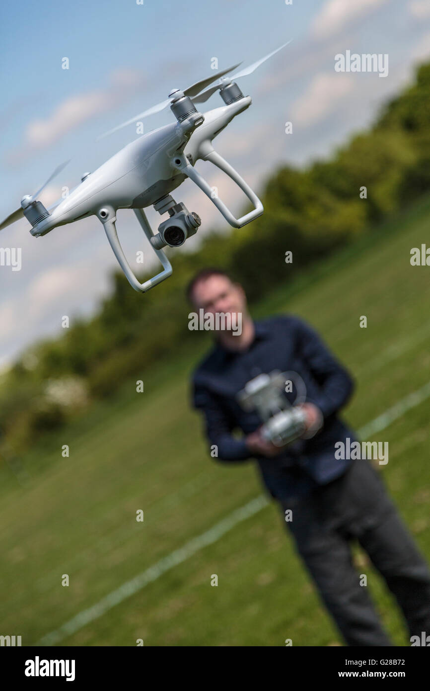 Close up image of a man flying a recreational drone / quadcopter in UK - Stock Image