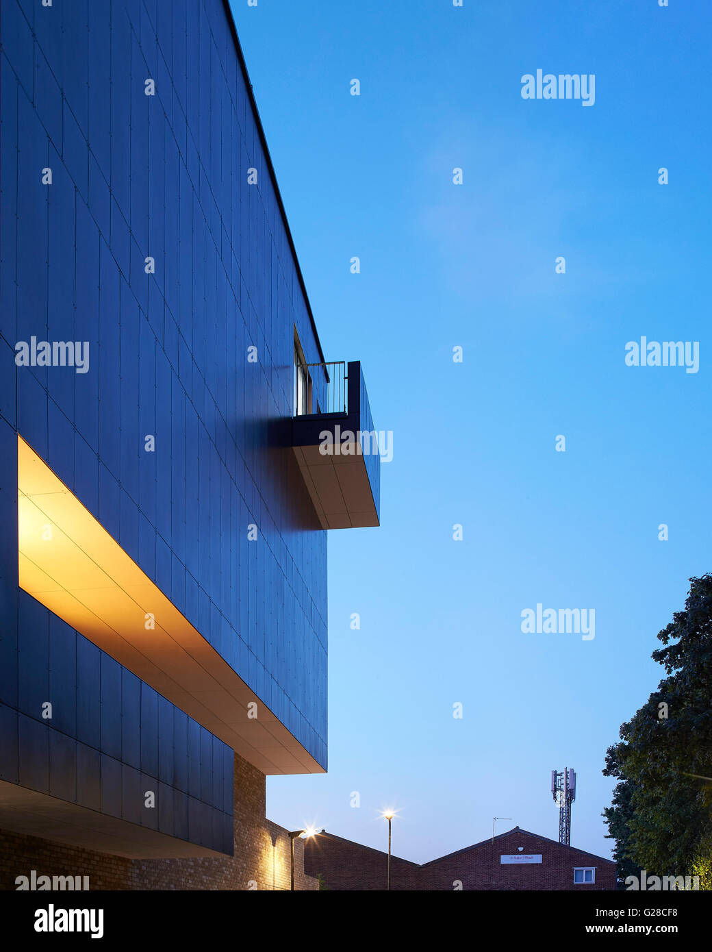 Building facade with singular balcony at dusk. Alpine Place, Brent, London, United Kingdom. Architect: Ayre Chamberlain - Stock Image