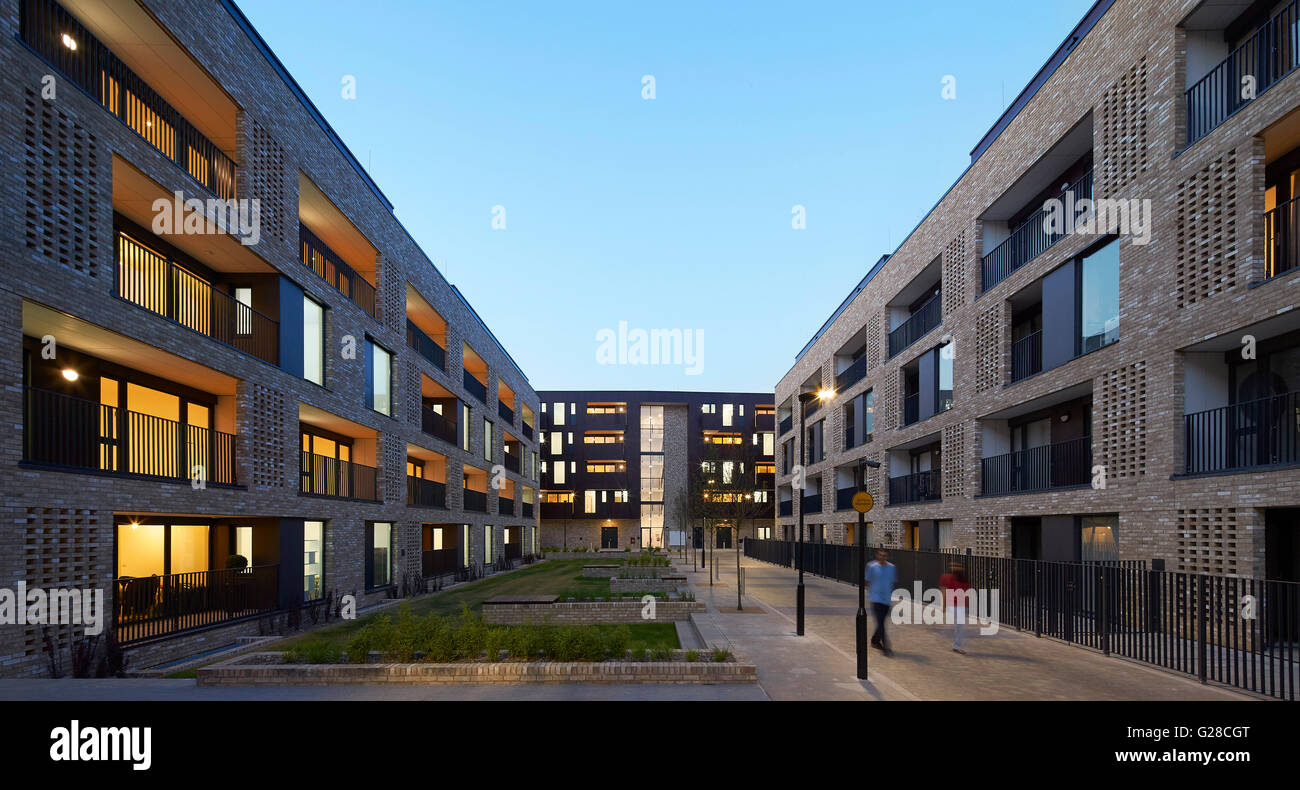 Housing complex with landscaped public realm and walkways at dusk. Alpine Place, Brent, London, United Kingdom. - Stock Image