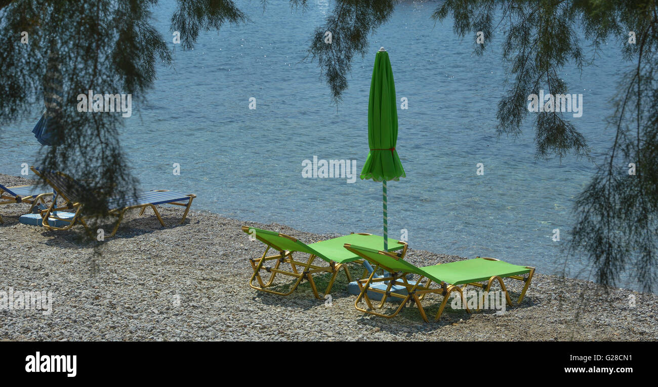 Two empty lime green sun loungers with a closed parasol sun shade on a shingle beach by the water's edge - Stock Image