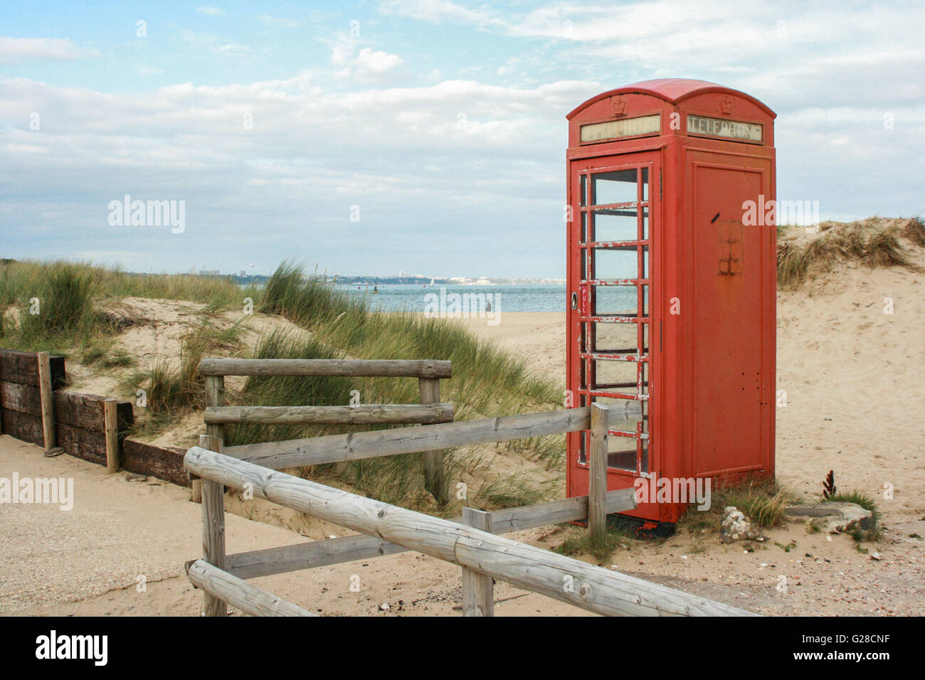 An old red telephone box stands among dunes on the edge of a sandy beach with a lone walker under a cloudy sky, - Stock Image