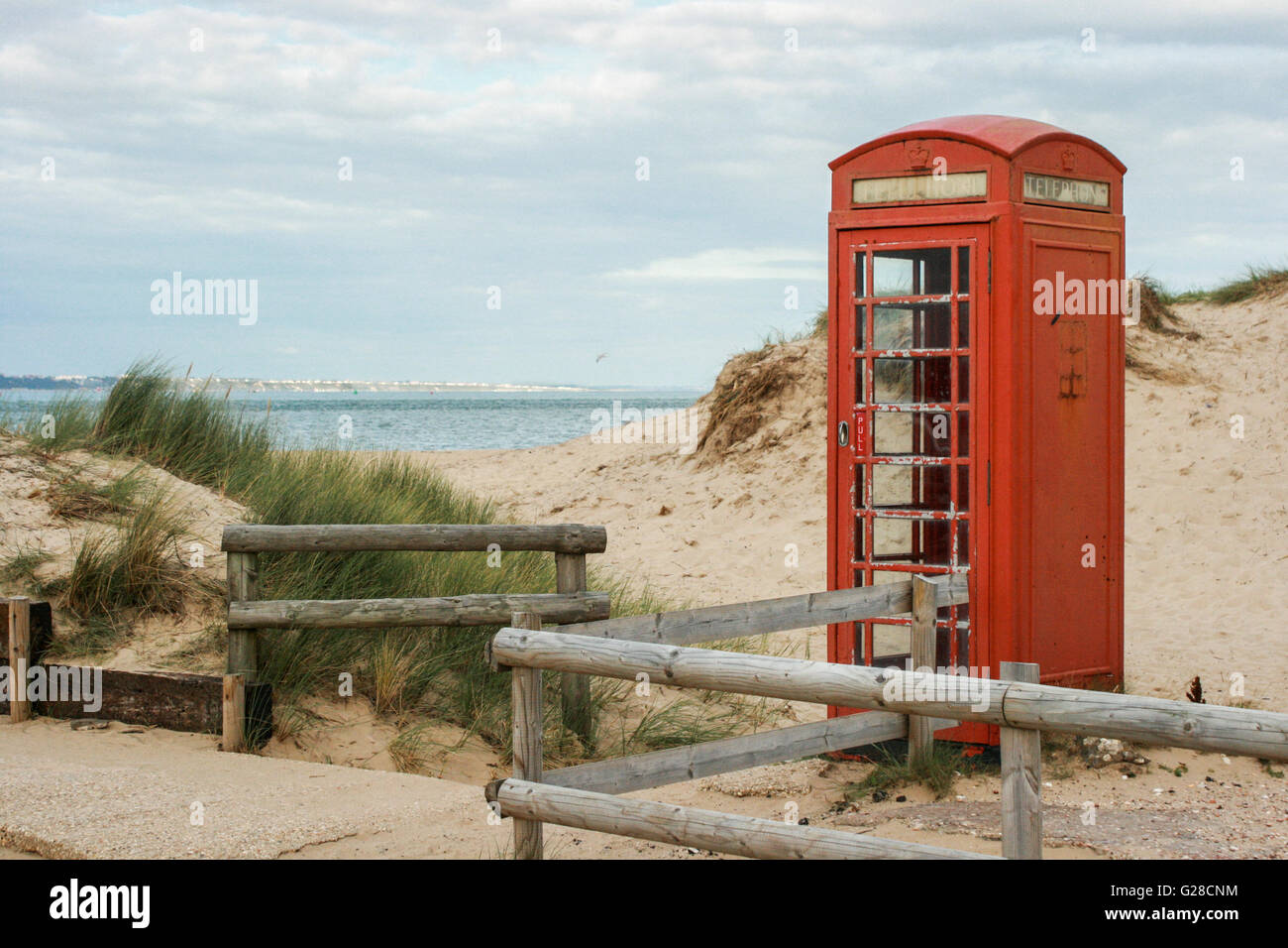 An old red telephone box stands among dunes on the edge of an empty sandy beach under a cloudy sky, UK - Stock Image