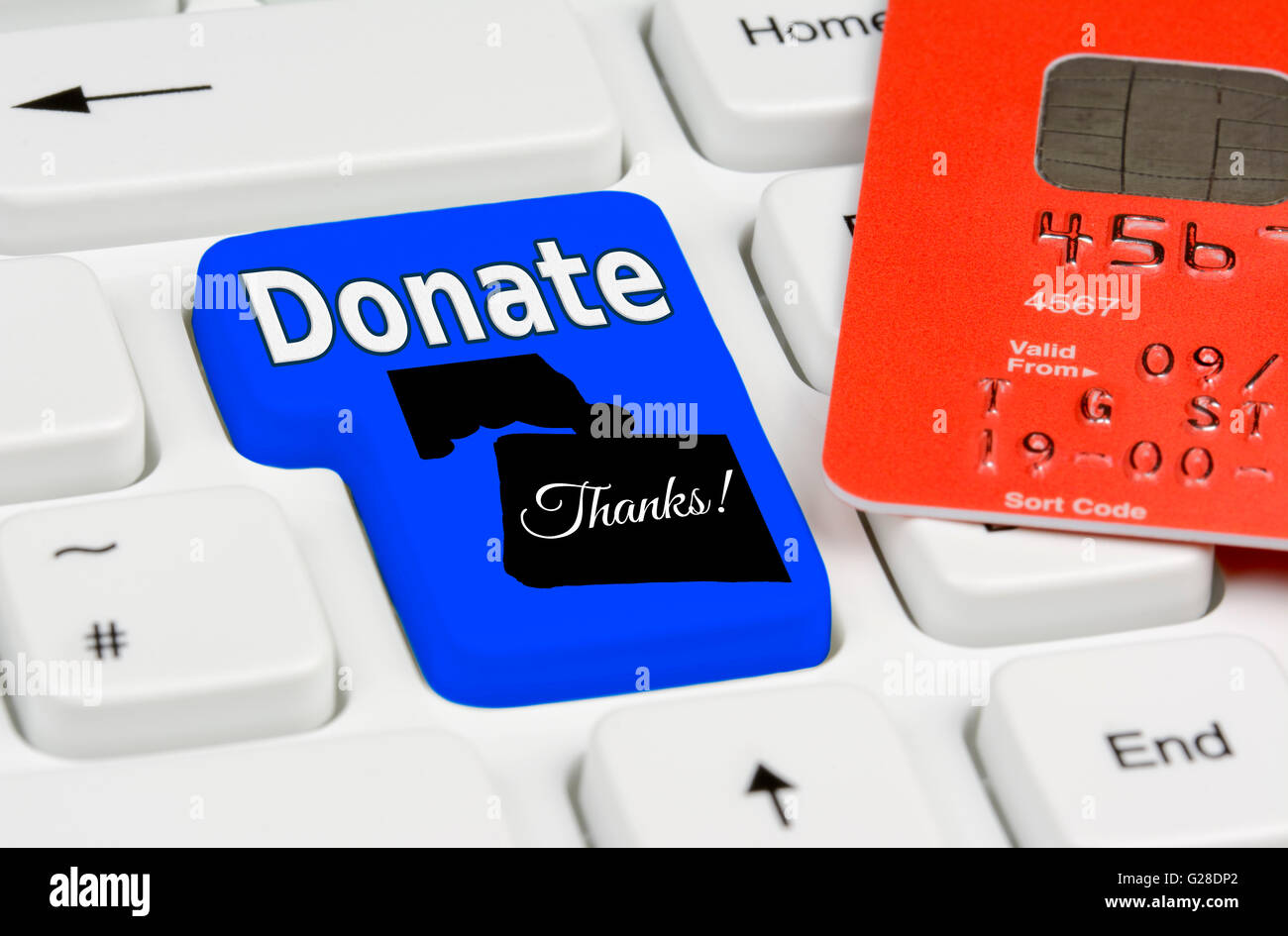 Donate button and payment card on a computer keyboard. - Stock Image