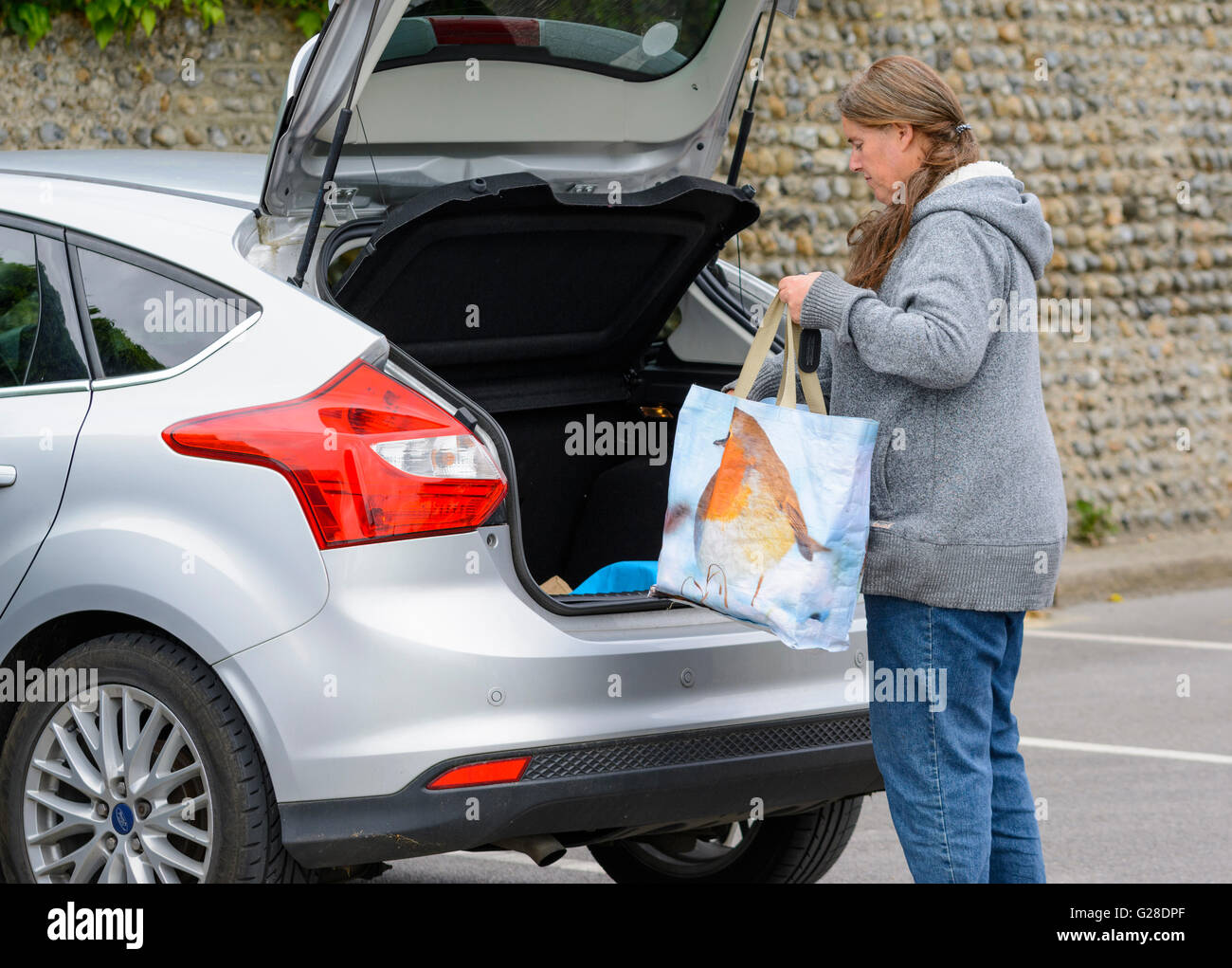 Middle aged woman loading up car with shopping. - Stock Image
