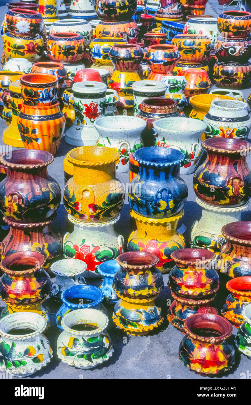 Bright sunshine reflects off the colorfully-painted pottery from Mexico displayed outdoors at an arts and crafts - Stock Image
