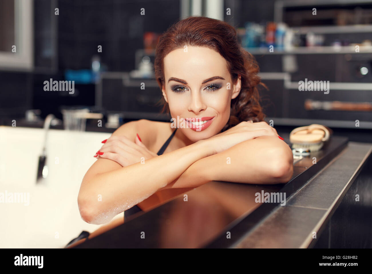 Woman elbowing on the edge of jacuzzi in bathroom - Stock Image