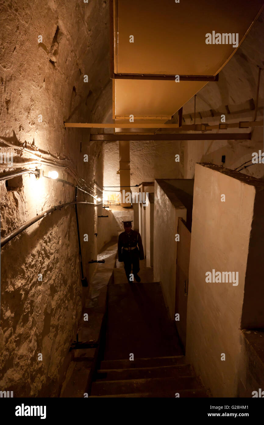 A site guide in British military fatigues in the underground tunnels used during World Wat II and later by NATO Stock Photo