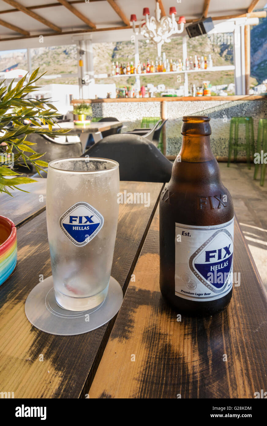 Greek FIX beer and glass on a table in a bar in Greece - Stock Image
