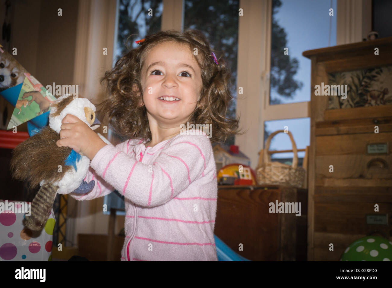 Birthday morning two year girl old still in pajamas in lounge happily clutches a soft toy bird present she has just - Stock Image