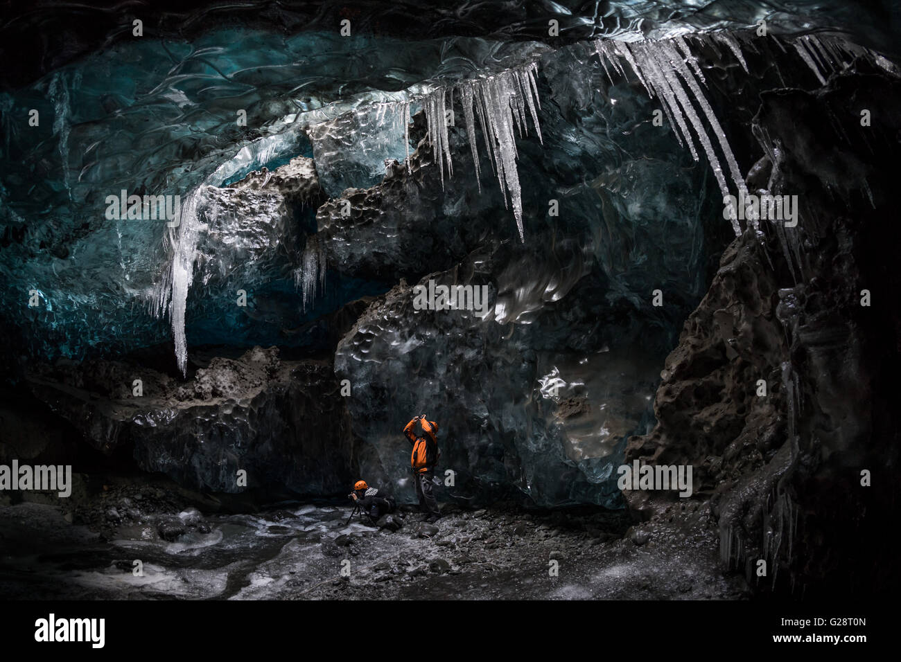 Tourists photographing in an ice cave, Vatnajokull, Iceland - Stock Image