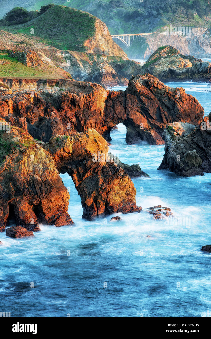 Evening glow along California's rugged Big Sur coastline with the Historic Rocky Creek Bridge on Highway One. - Stock Image