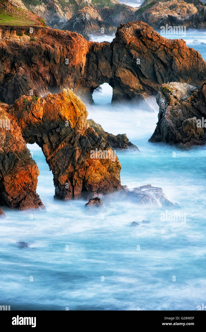 Evening glow on the many sea stacks and sea arches along California's rugged Big Sur coastline. - Stock Image