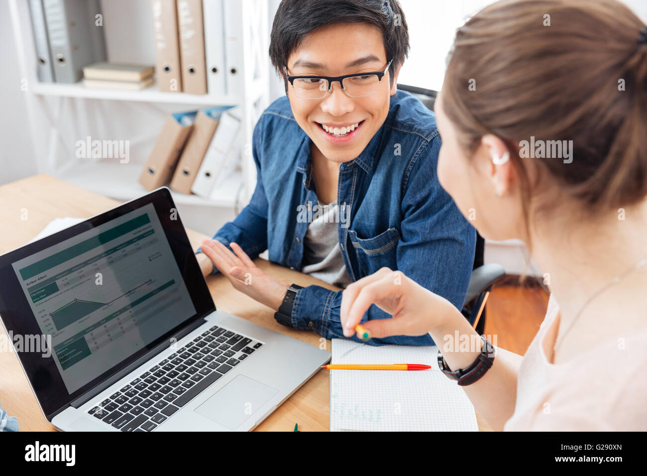 Two happy young businesspeople using laptop and working together - Stock Image