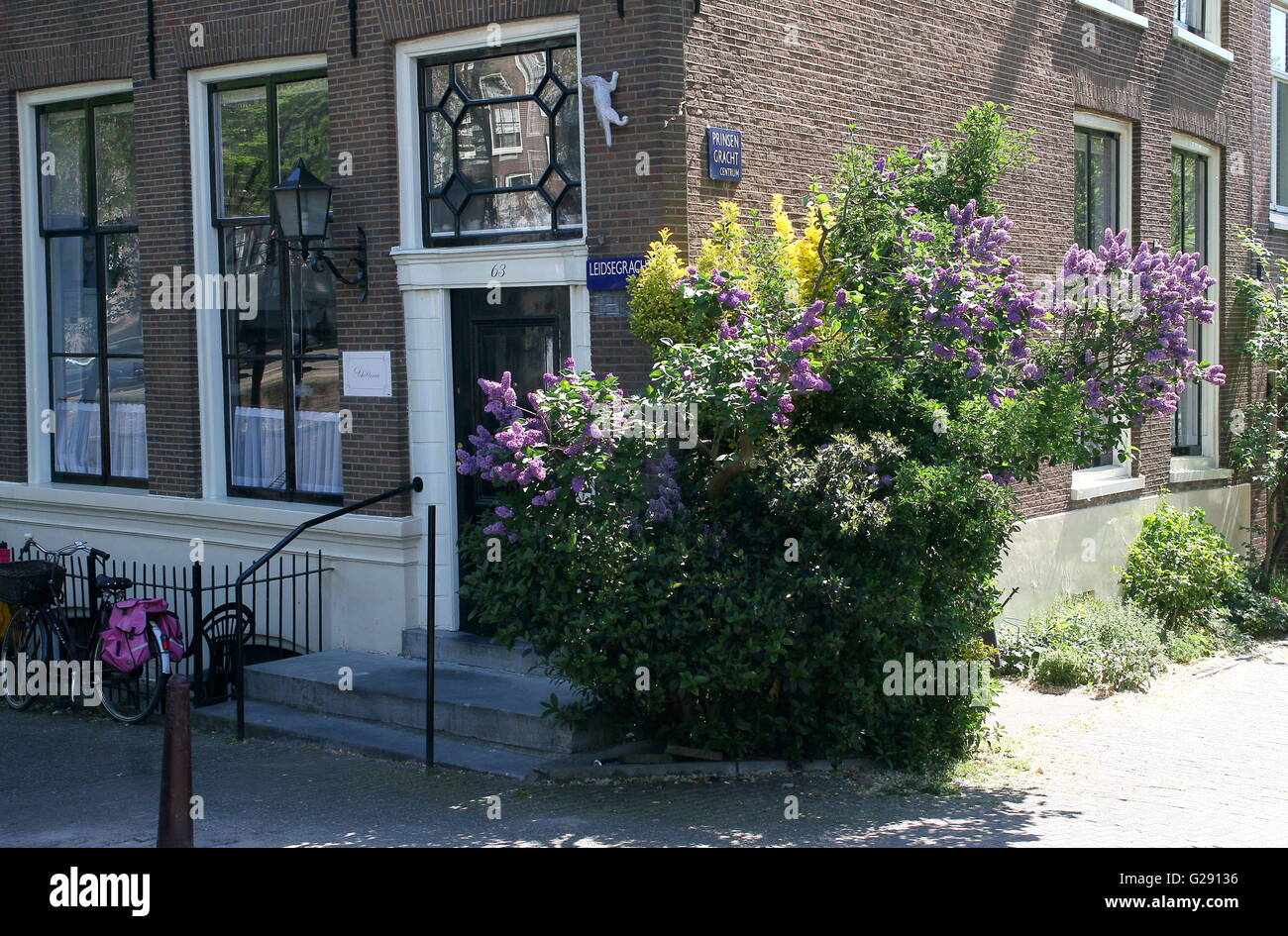 Old Amsterdam canal house with springtime flowers. Corner Leidsegracht and Prinsengracht canal, central Amsterdam, - Stock Image