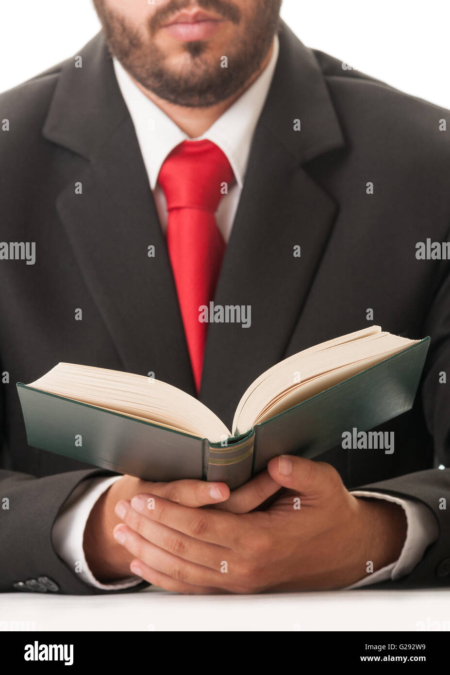 Lawyer dress with black suit and red tie reading book of laws - Stock Image