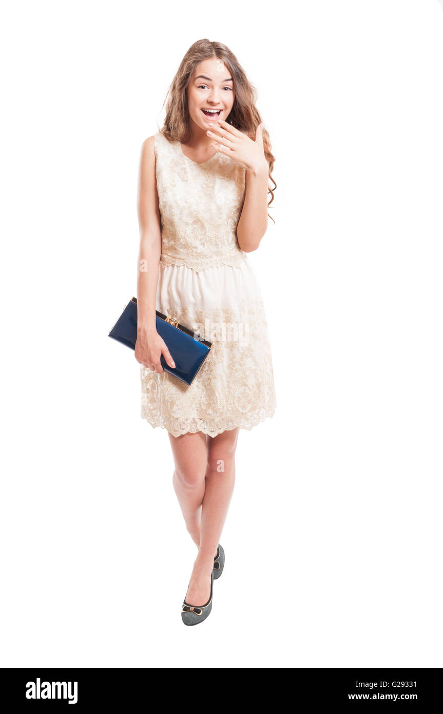 Long hair female model acting surprised while wearing a beautiful lace dress - Stock Image