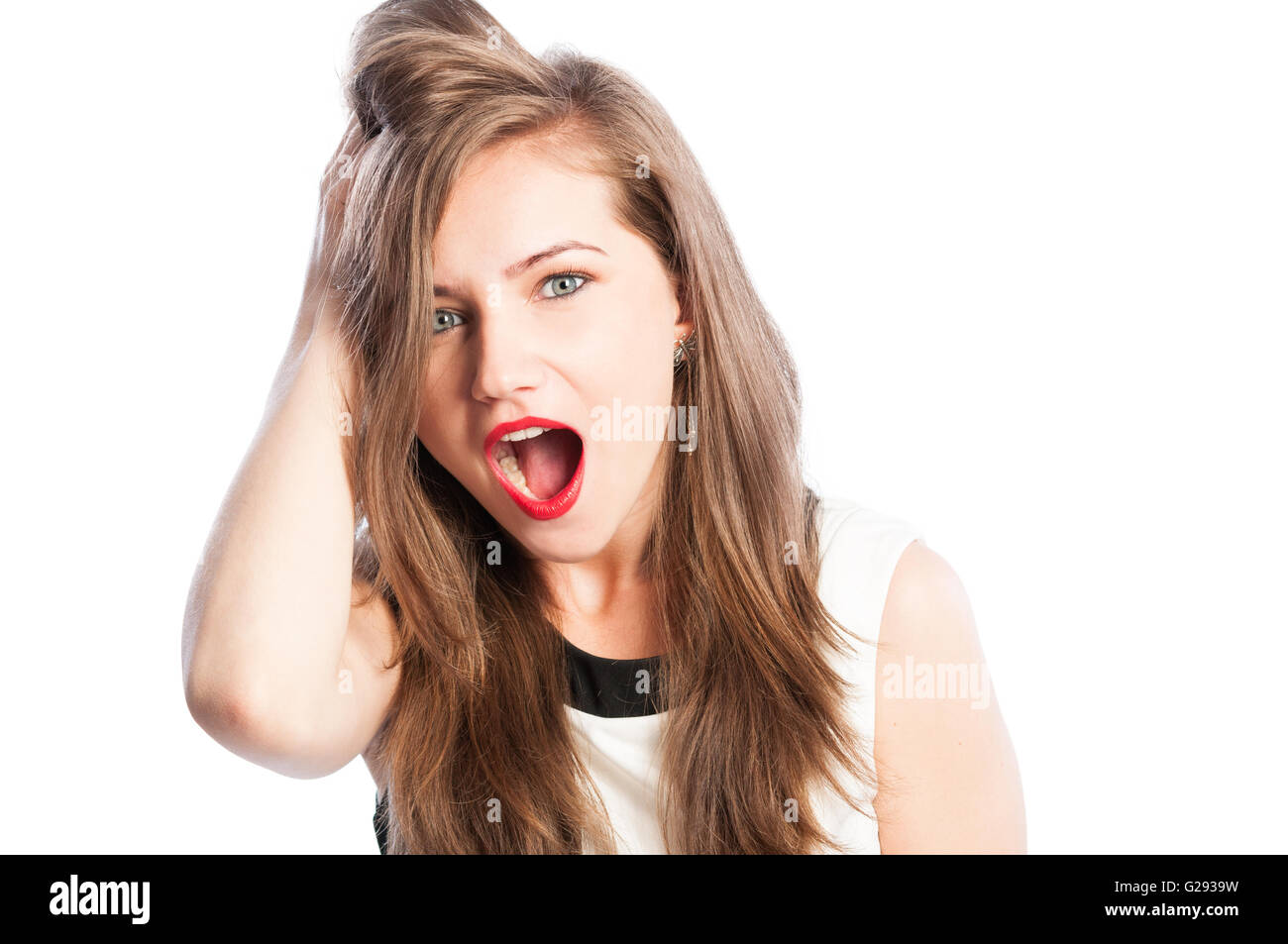 Female model amazed, surprised and astonished, grabbing her hair - Stock Image
