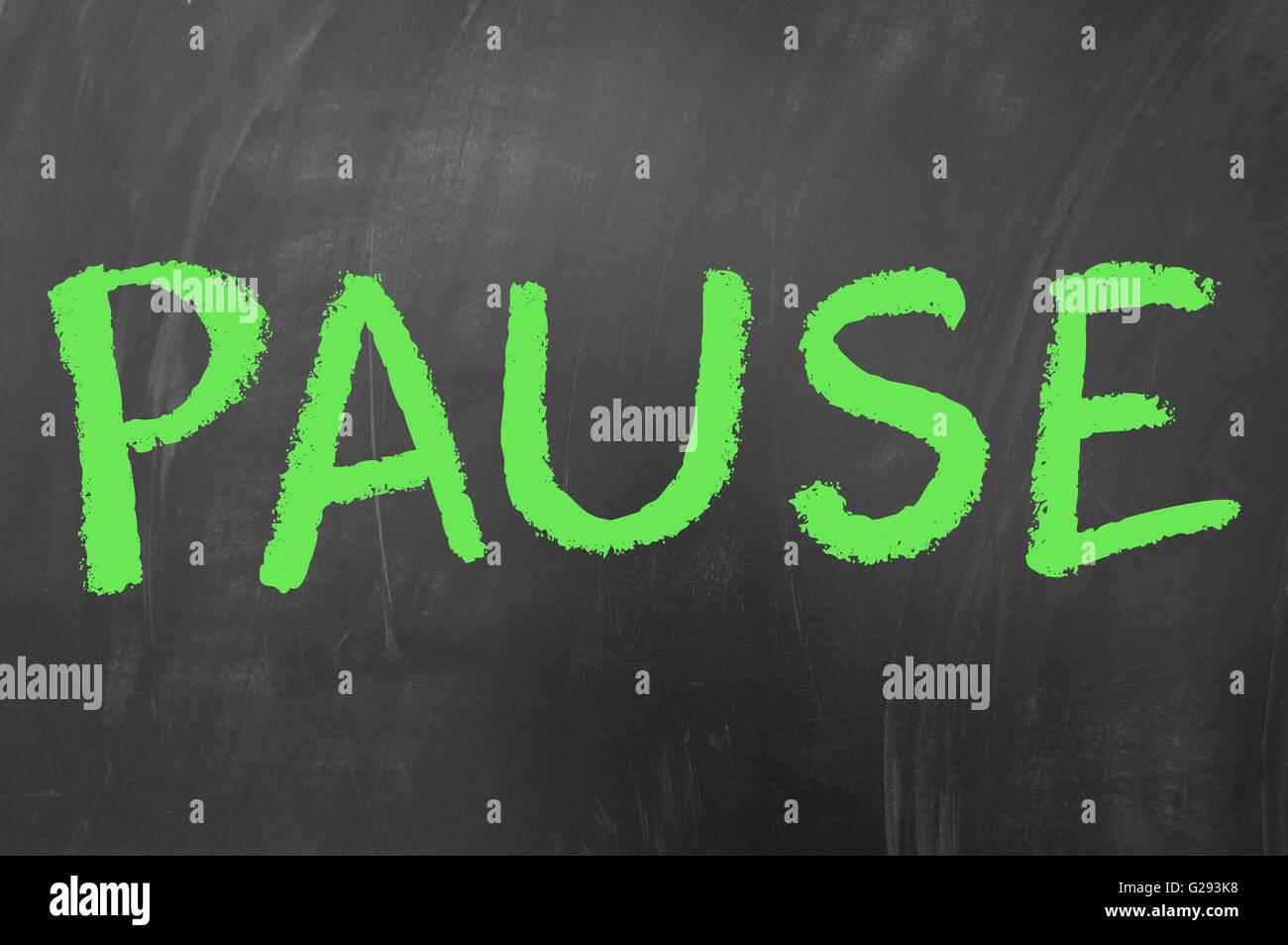 Pause word written wth green chalk on school blackboard - Stock Image