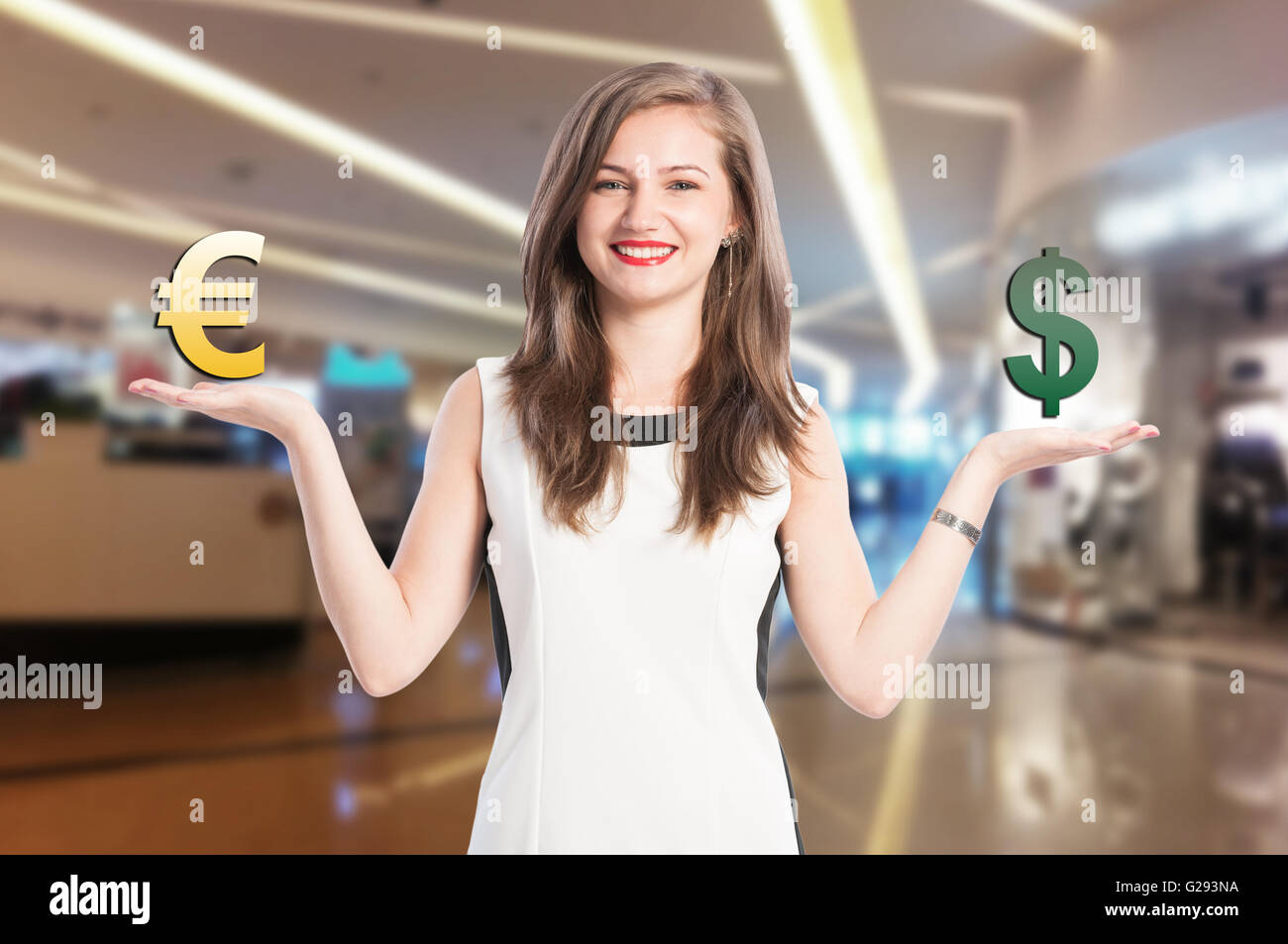 Woman holding and scaling euro and dollar sign with fade mall background - Stock Image