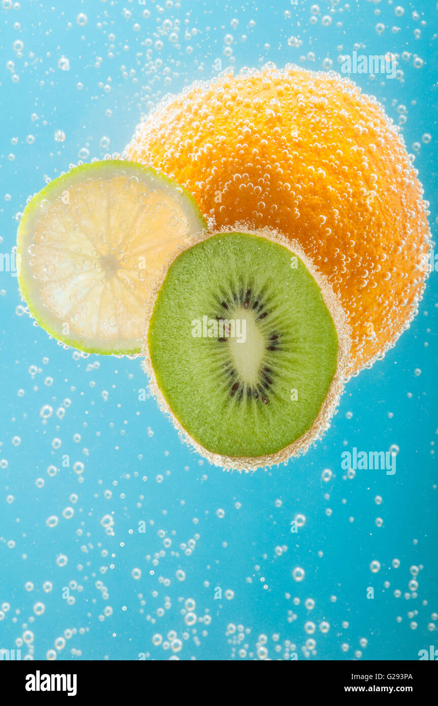 Fruits like orange, kiwi and lime in water with bubbles - Stock Image