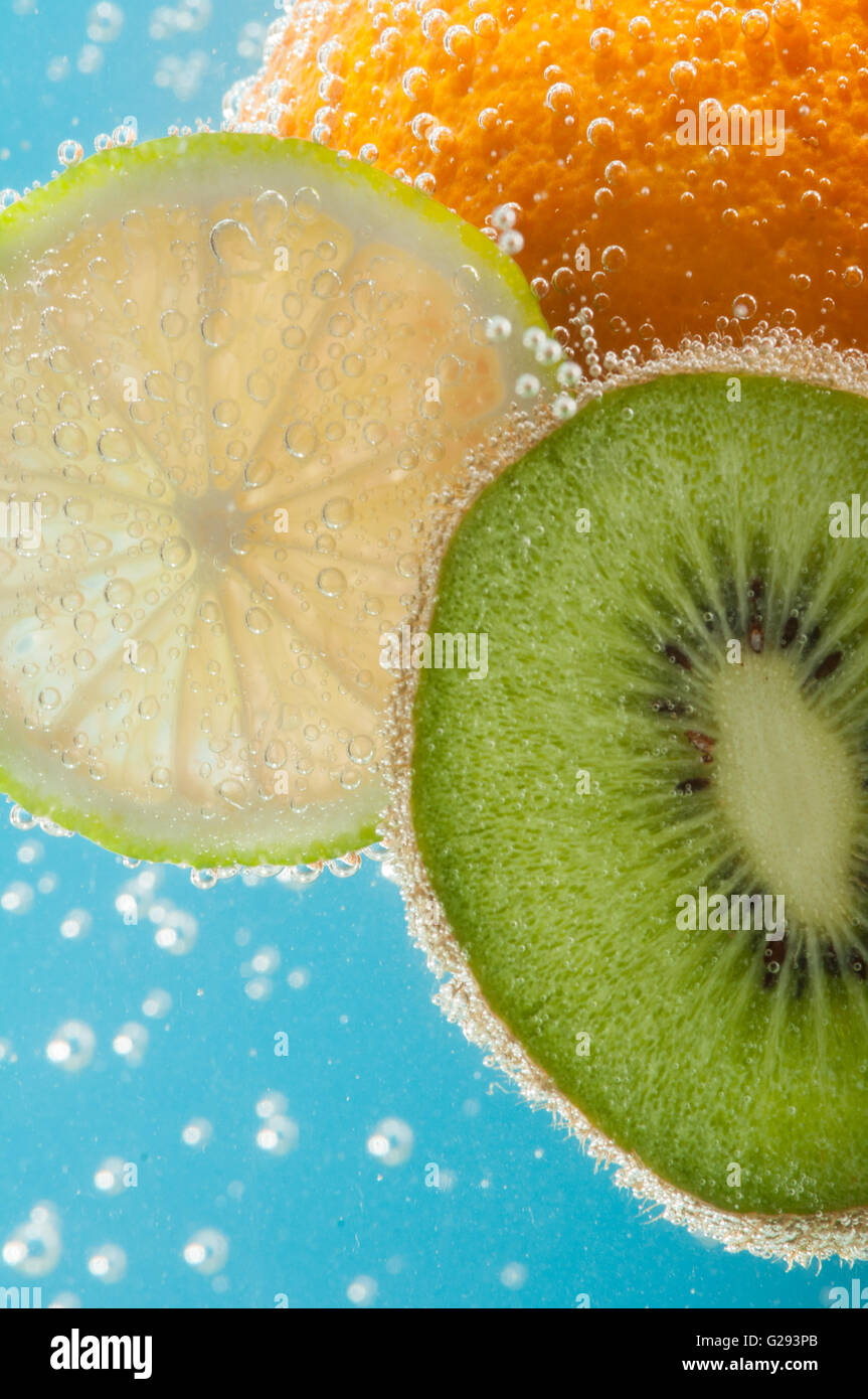 Fruits like orange, kiwi and lime in water with bubbles closeup - Stock Image