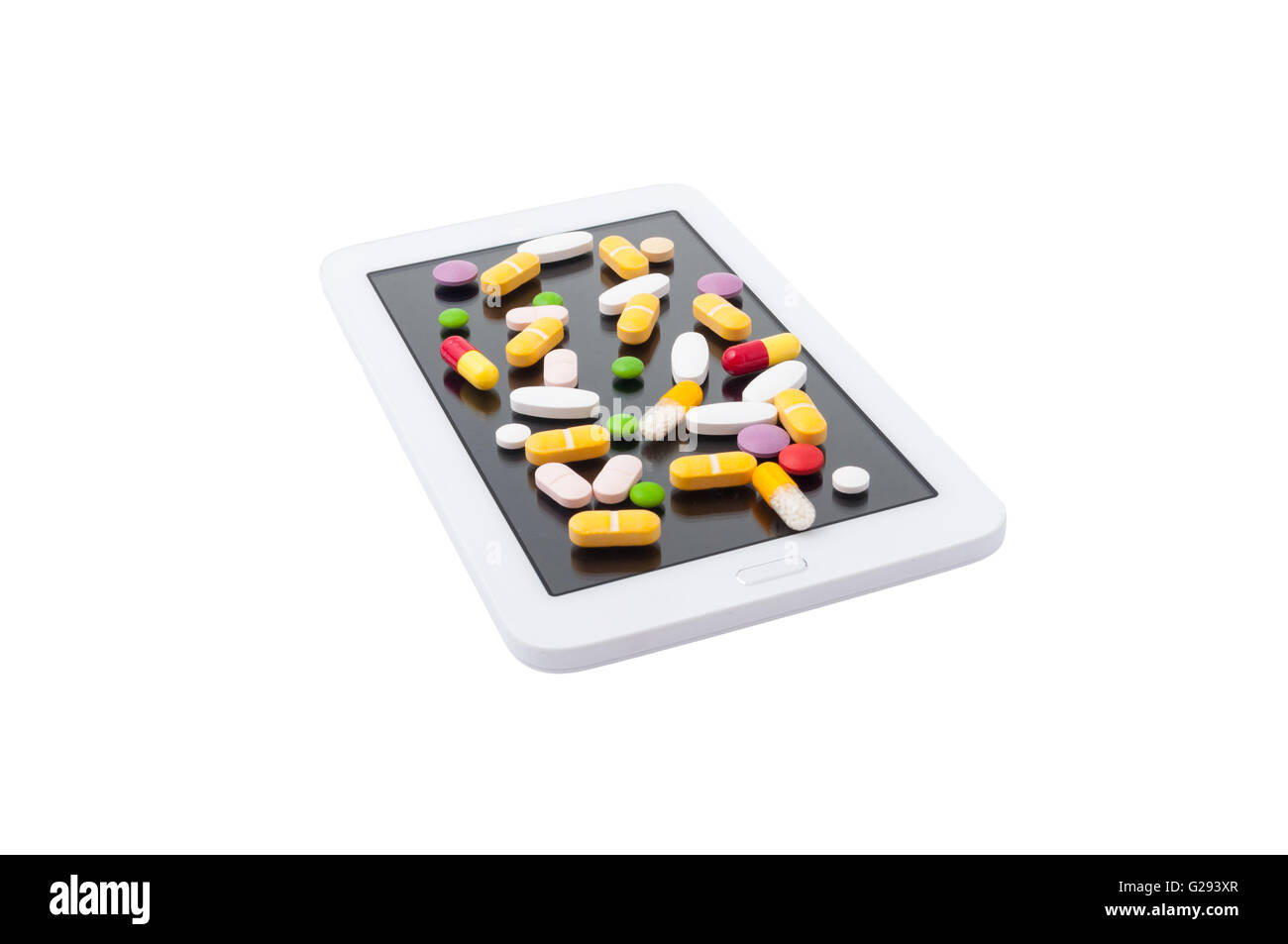 Bunch of colored pills on a touchscreen tablet isolated white background - Stock Image