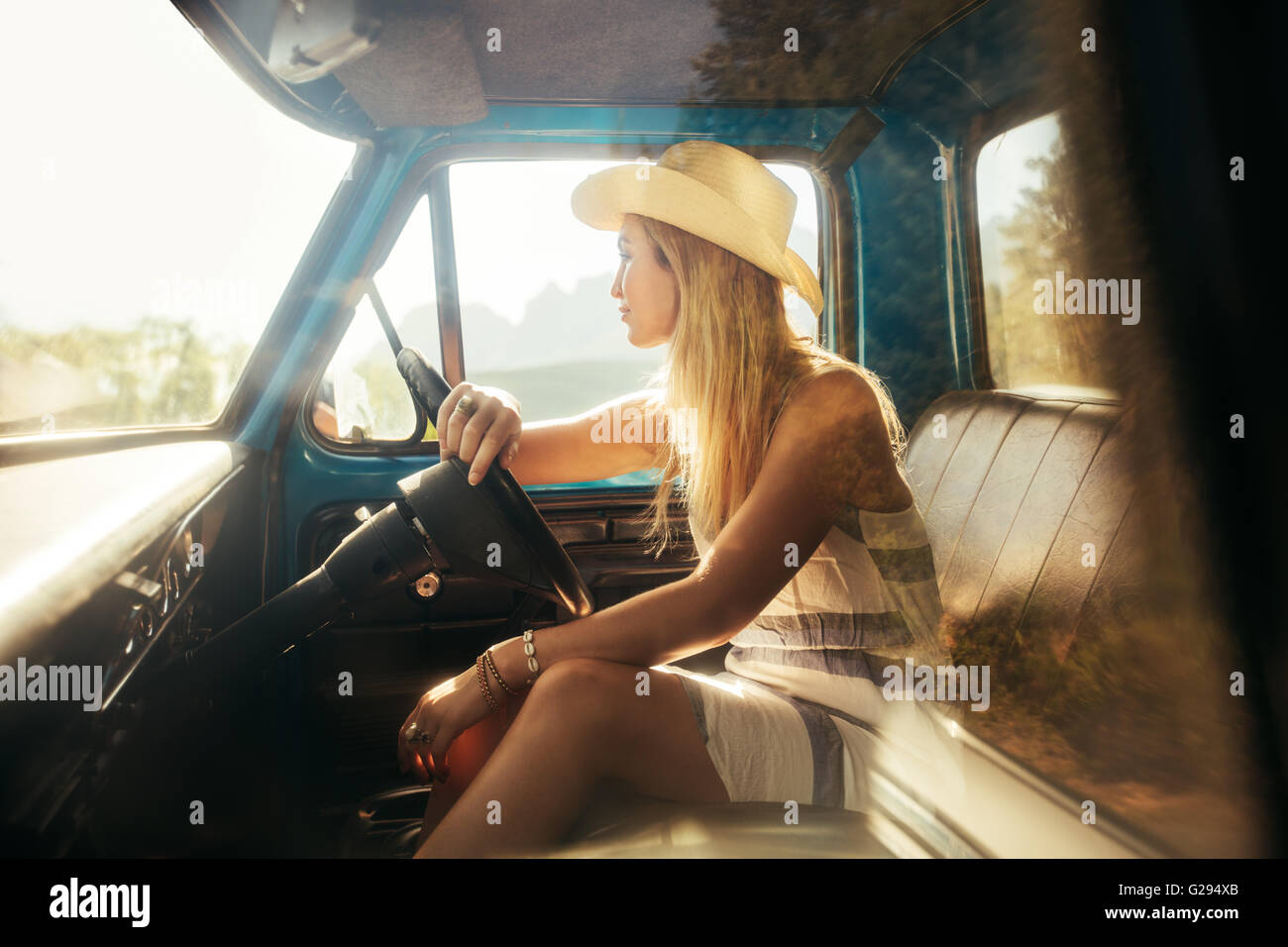 Portrait of young woman sitting on driving seat of a car and looking away. Girl wearing hat on a road trip. - Stock Image