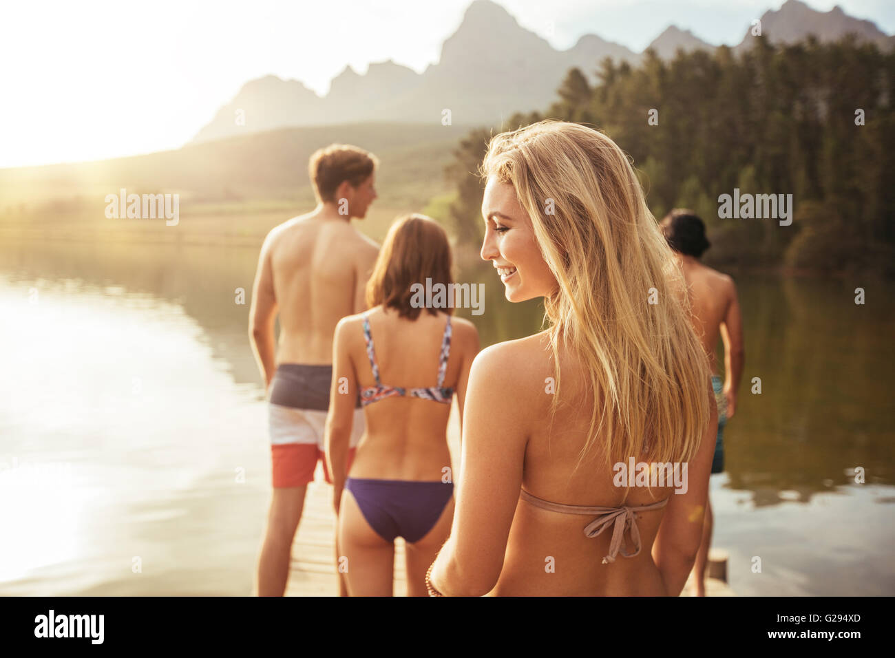 Rear view of an attractive young woman walking with friends on a jetty. Young people enjoying at the lake on a summer - Stock Image