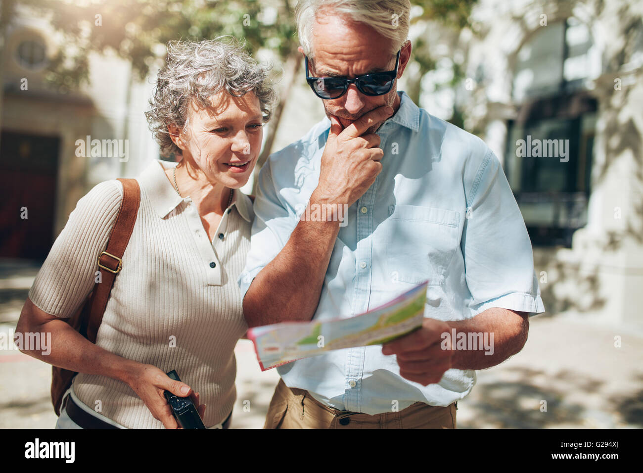 Senior couple looking at a map while sightseeing. Couple of mature tourist using city map on their vacation. - Stock Image