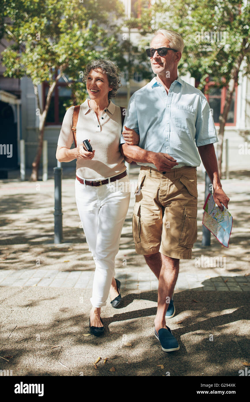 Mature couple walking around the city holding a map. Happy senior man and woman on a vacation. - Stock Image