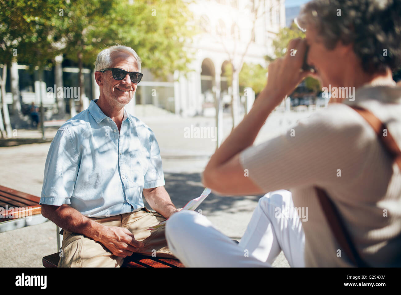 Handsome senior man being photographed by his wife. Senior tourist talking photos with camera outdoors in the city. - Stock Image